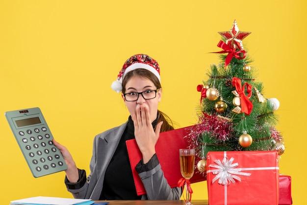 Vue de face fille choquée avec chapeau de noël assis à la table en regardant la calculatrice mettre la main