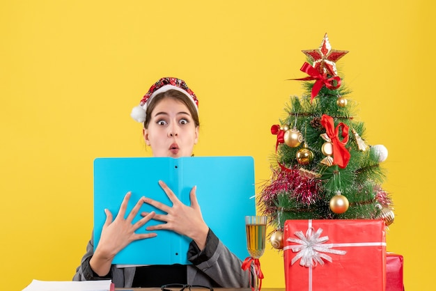 Vue de face fille choquée avec chapeau de noël assis à la table tenant le dossier de document avec les deux mains arbre de noël et cocktails de cadeaux