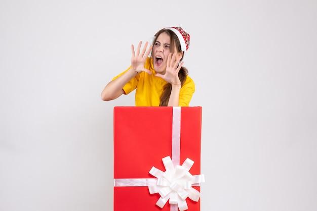 Vue de face fille en colère avec bonnet de noel criant derrière gros cadeau de noël