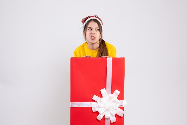 Vue de face fille en colère avec bonnet de noel debout derrière une grande boîte-cadeau de noël