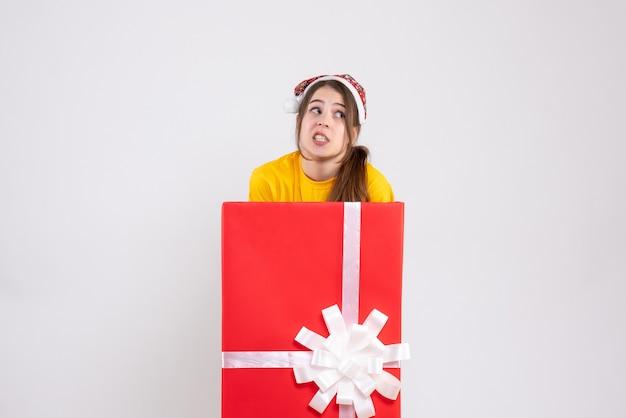Vue de face fille confuse avec bonnet de noel debout derrière un grand cadeau de noël