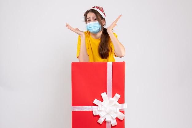 Vue de face fille confuse avec bonnet de noel et masque médical debout derrière un grand cadeau de noël
