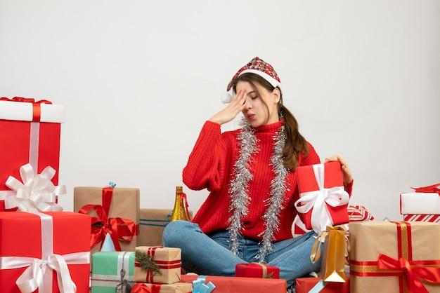 Vue de face fille confuse avec bonnet de noel tenant un cadeau assis autour de cadeaux