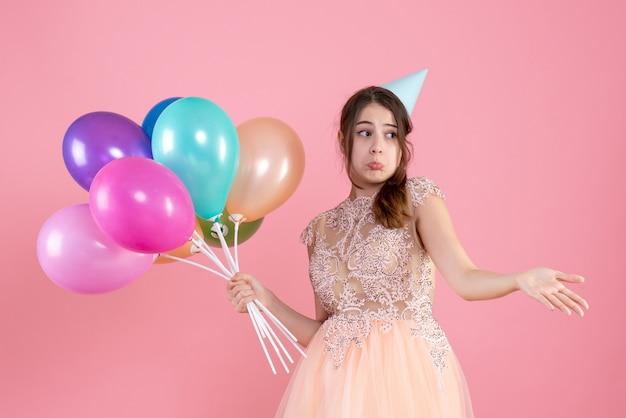 Vue de face fille confuse avec chapeau de fête ouvrant sa main tenant des ballons
