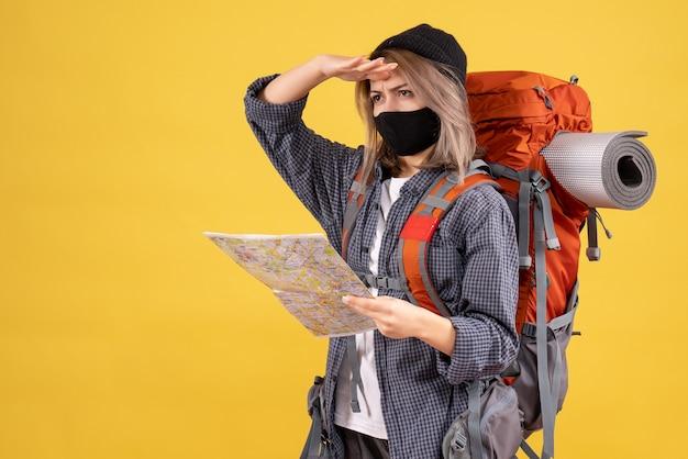 Vue de face de fille cool voyageur avec masque noir et sac à dos tenant la carte en regardant quelque chose