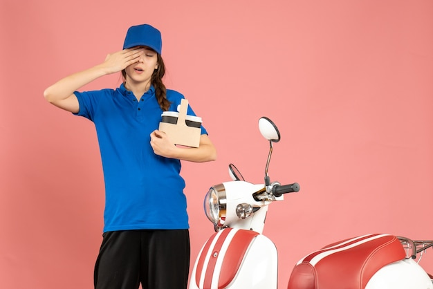 Vue de face d'une fille de coursier réfléchie debout à côté d'une moto tenant un café sur fond de couleur pêche pastel