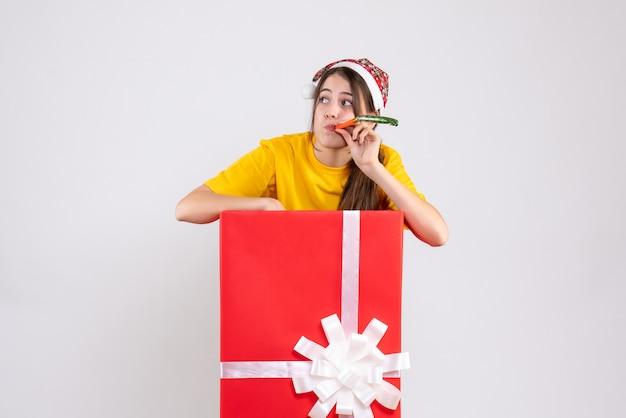Vue de face fille curieuse avec bonnet de noel à l'aide de bruiteur debout derrière un grand cadeau de noël