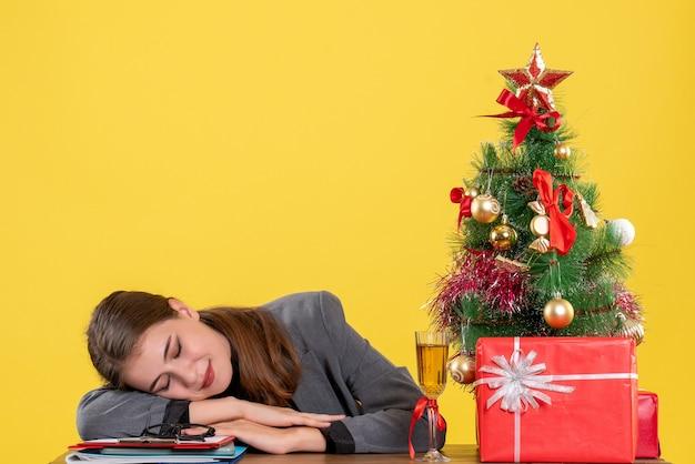 Vue de face fille endormie assis au bureau mettant la tête