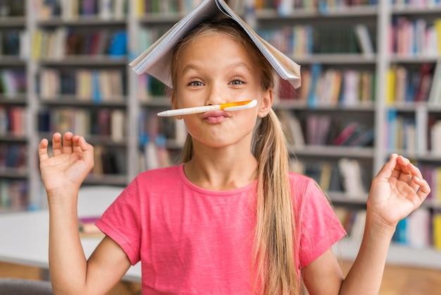 Vue de face fille étant idiot dans la bibliothèque