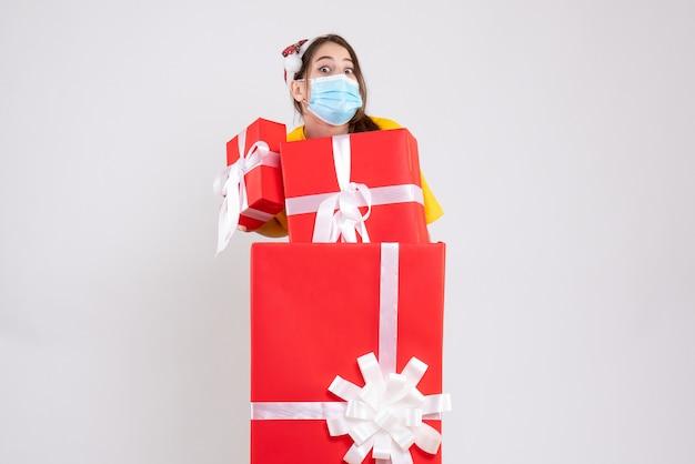 Vue de face fille exaltée avec bonnet de noel tenant ses cadeaux debout derrière un grand cadeau de noël