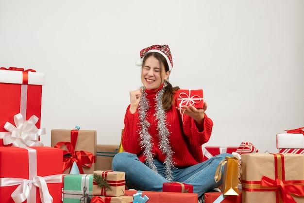 Vue de face fille exaltée avec bonnet de noel tenant son cadeau tout en se réjouissant assis autour de cadeaux