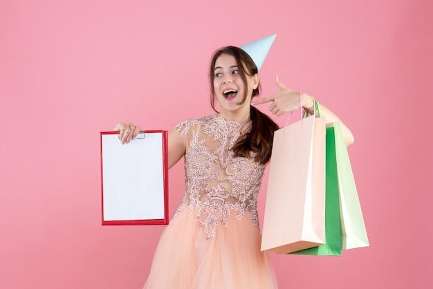 Vue de face fille exaltée avec chapeau de fête tenant des documents et des sacs à provisions pointant sur elle-même