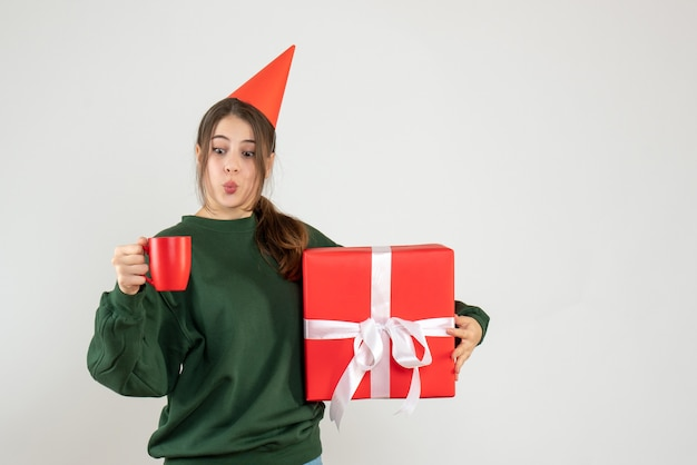 Vue de face fille excitée avec chapeau de fête tenant son cadeau de noël et une tasse