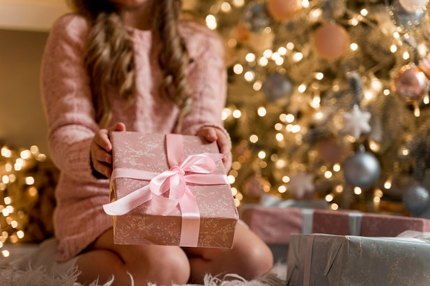 Vue de face d'une fille heureuse avec des cadeaux et arbre de noël