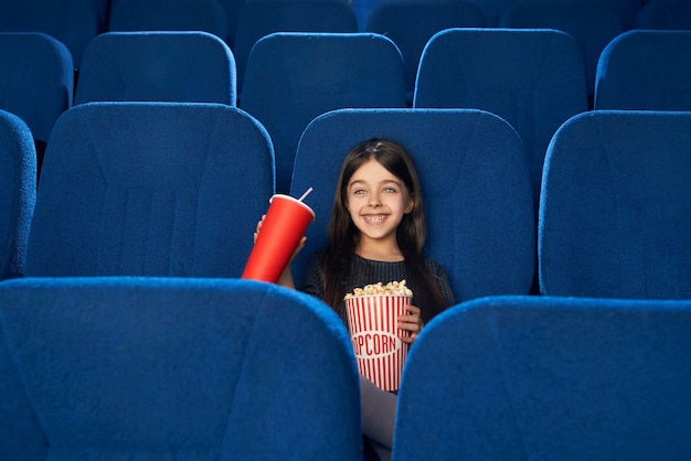 Vue de face d'une fille heureuse en regardant un film drôle dans une salle de cinéma