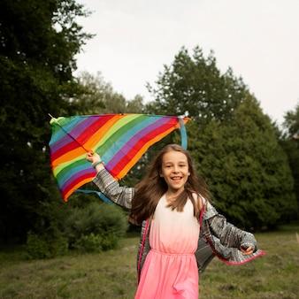 Vue de face d'une fille heureuse s'amuser avec un cerf-volant
