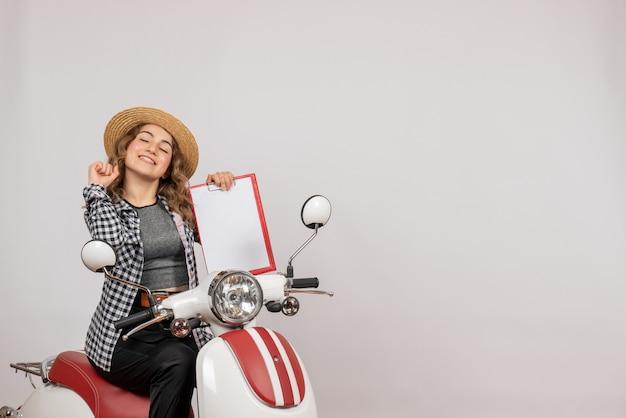 Vue de face de la fille heureuse de voyageur sur le cyclomoteur tenant le presse-papiers rouge