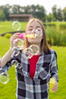 Vue de face fille jouant avec des bulles de savon