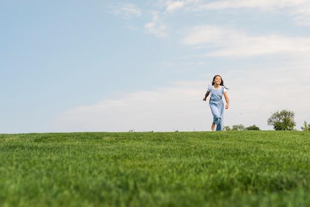 Vue de face fille marchant pieds nus sur l'herbe