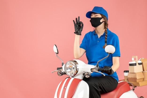 Vue de face d'une fille de messagerie rêveuse portant un masque médical et des gants assis sur un scooter livrant des commandes sur fond pêche pastel