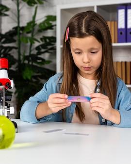 Vue de face de fille avec microscope et tubes à essai