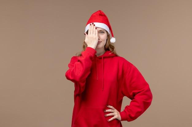 Vue de face fille de noël couvrant son visage sur fond marron vacances modèle noël