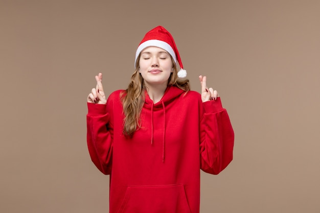 Vue de face fille de noël croisant ses doigts sur fond marron vacances modèle noël