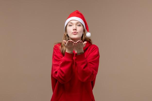 Vue de face fille de noël envoi de bisous d'air sur fond marron femme vacances noël