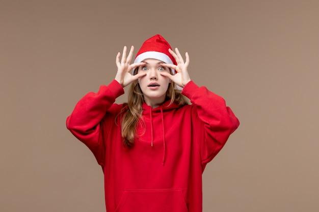 Vue de face fille de noël ouvrant les yeux sur fond marron vacances noël émotion