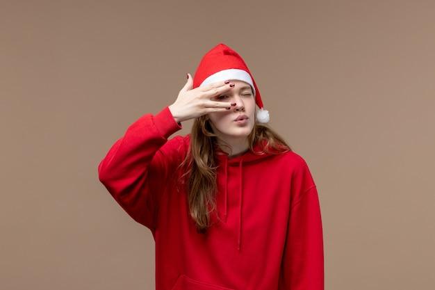 Vue de face fille de noël posant sur fond marron vacances noël émotion