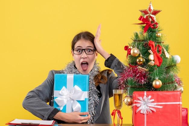 Vue de face fille perplexe avec des lunettes assis à la table mettant la main