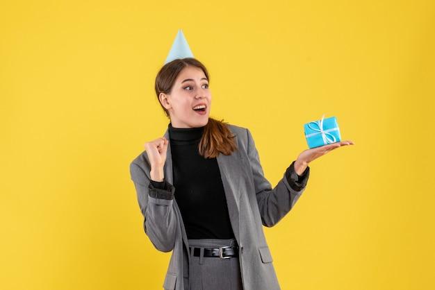 Vue de face fille ravie avec chapeau de fête tenant son cadeau