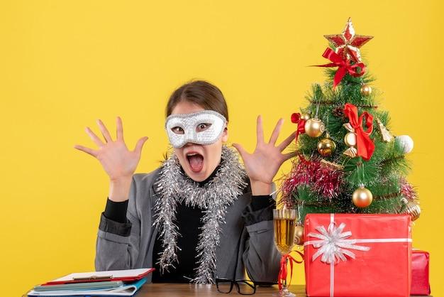 Vue de face fille ravie avec masque assis à la table ouvrant les deux mains arbre de noël et cocktails cadeaux