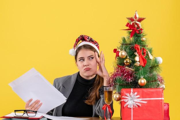 Vue de face fille réfléchie avec chapeau de noël assis à la table mettant la main