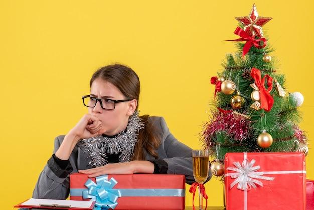 Vue de face fille réfléchie avec des lunettes assis à la table en pensant près de l'arbre de noël et des cadeaux cocktail