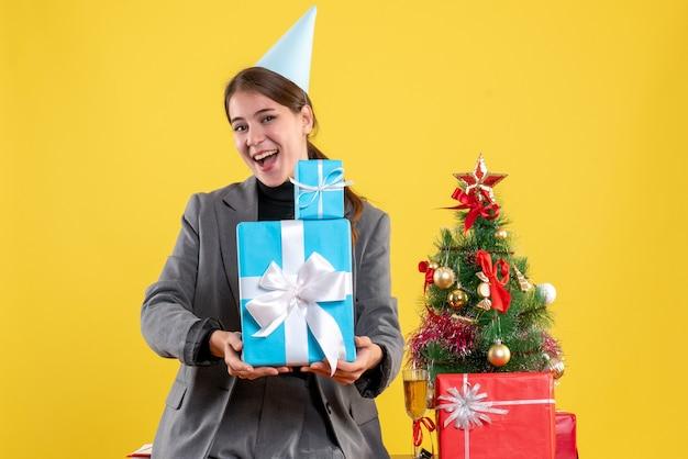 Vue de face fille réjouie avec chapeau de fête tenant des cadeaux de noël avec les deux mains près de l'arbre de noël et des cadeaux cocktail