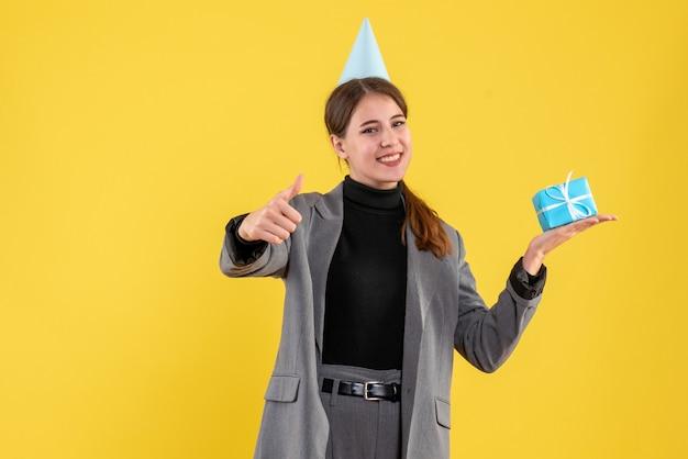 Vue de face fille réjouie avec chapeau de fête tenant son cadeau faisant signe de pouce vers le haut