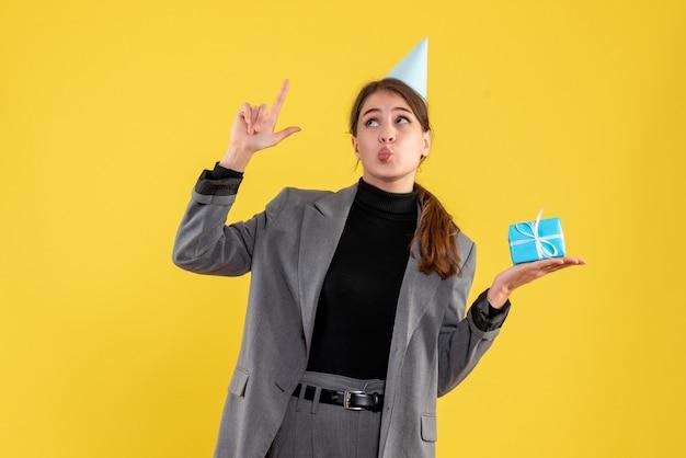 Vue de face fille réjouie avec chapeau de fête tenant son cadeau pointant avec le doigt vers le haut