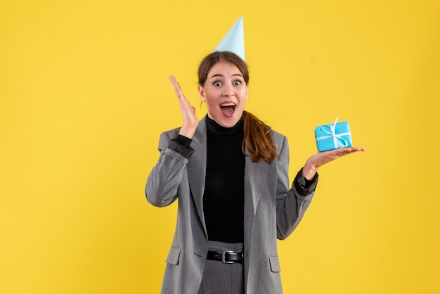 Vue de face fille réjouie avec chapeau de fête tenant son cadeau