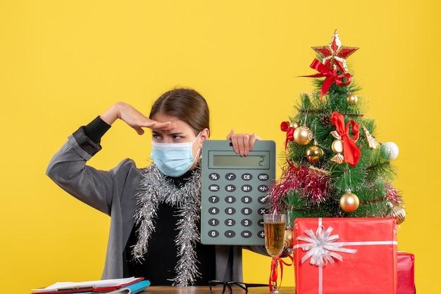 Vue de face fille sérieuse avec masque médical assis à la table tenant la calculatrice mettant la main