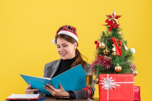 Vue de face fille souri avec chapeau de noël assis à la table à la recherche de documents dans le dossier bleu arbre de noël et cadeaux cocktail