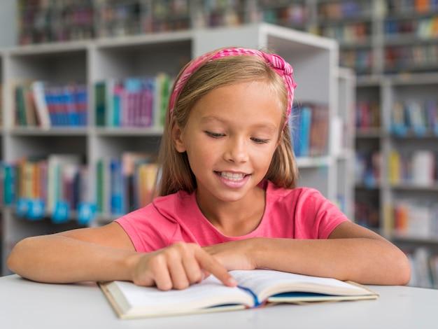 Vue de face, fille souriante, faire ses devoirs dans la bibliothèque