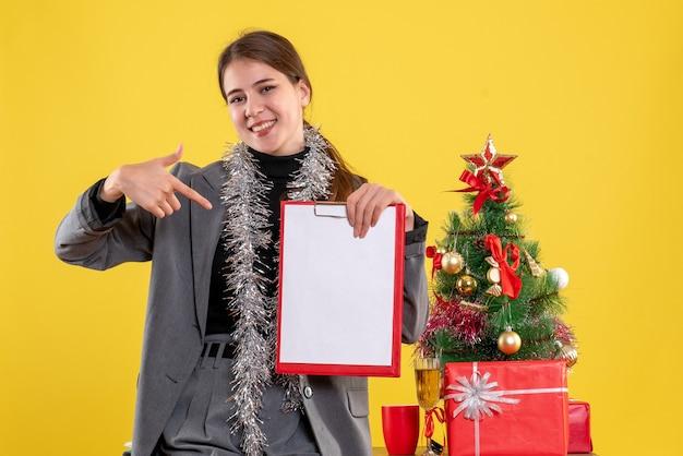 Vue de face fille sourit montrant des documents debout près de l'arbre de noël et des cadeaux cocktail