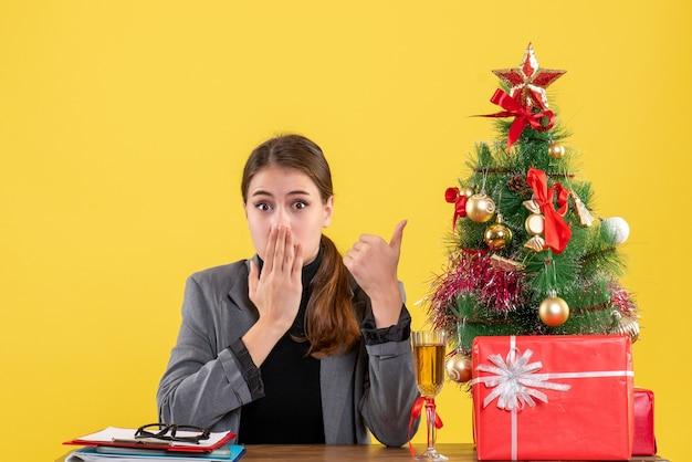Vue de face fille surprise assise au bureau mettant la main