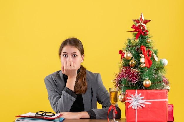Vue de face fille surprise assise au bureau a mis la main à sa bouche arbre de noël et cadeaux cocktail