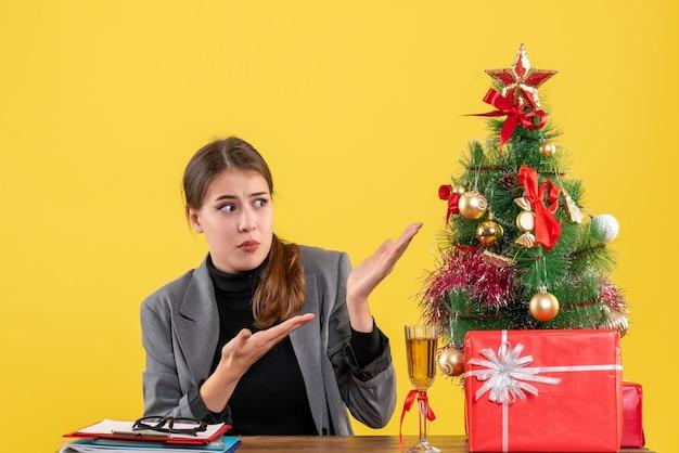 Vue de face fille surprise assise au bureau montrant un arbre de noël et un cocktail de cadeaux