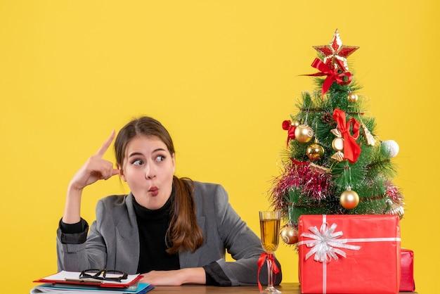 Vue de face fille surprise assise à la table montrant quelque chose d'arbre de noël et de cadeaux cocktail