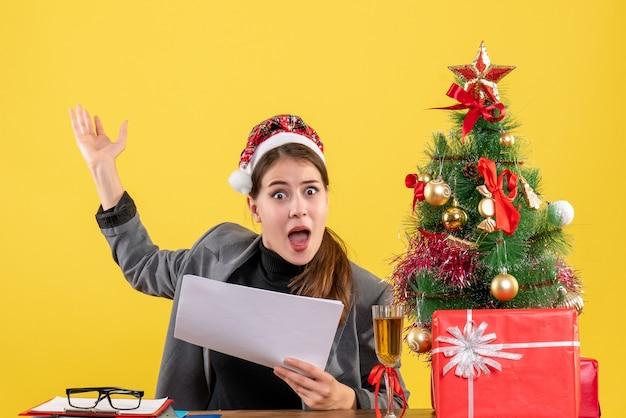 Vue de face fille surprise avec chapeau de noël assis à la table de noël arbre et cadeaux cocktail