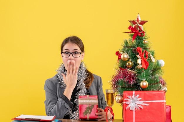 Vue de face fille surprise avec des lunettes assis à la table mettant la main à sa bouche arbre de noël et cadeaux cocktail