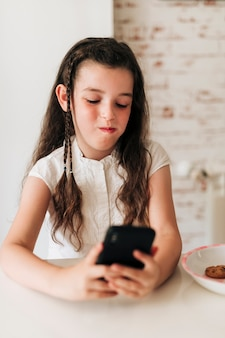 Vue de face fille avec téléphone et bouche pleine de biscuits